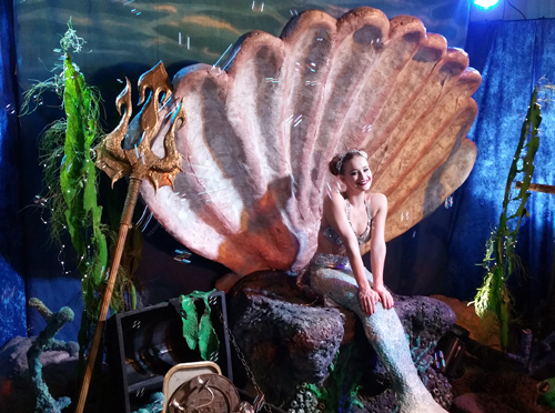 Undersea theme props for rent, giant clam shell and coral for mermaid to sit in shown here with a mermaid on the shell during a party
